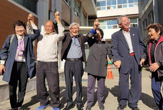 지난해 10월 49년 만에 무죄를 선고받은 영창호 선원 정삼근씨 등 2명과 고인이 된 강인준씨와 유재철씨의 유가족들이 만세를 부르고 있다. [뉴스1]