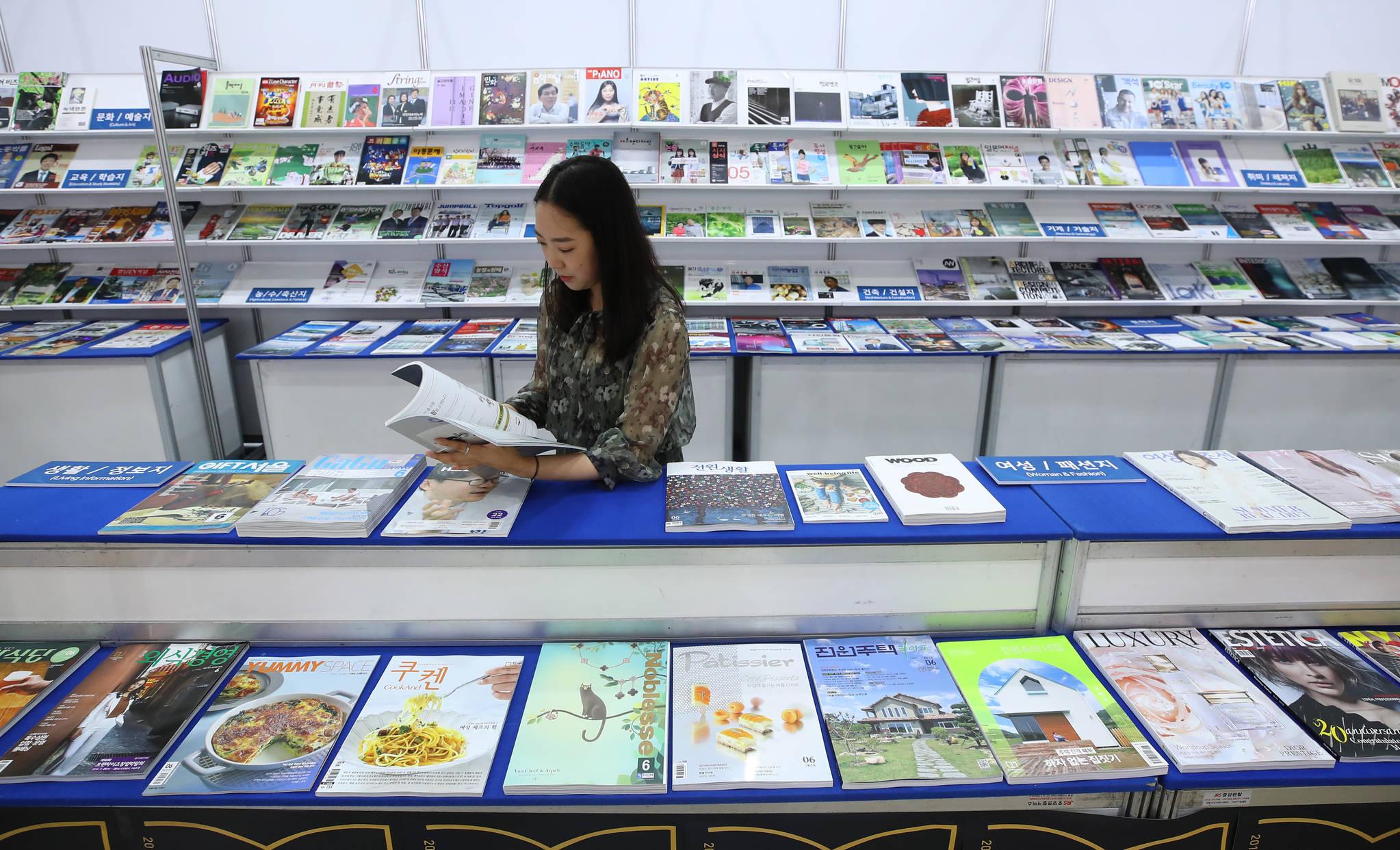 지난달 열린 '서울국제도서전'에서 한국잡지협회 부스를 찾은 한 관람객이 잡지를 읽고 있다. 잡지는 제한적으로 담배 광고를 게재할 수 있다. [연합뉴스]