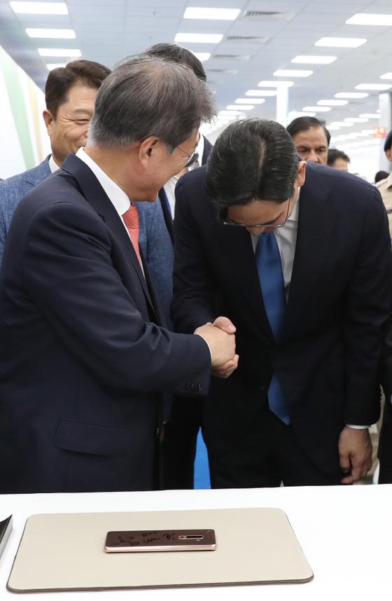 문재인 대통령이 9일 인도 삼성 공장 준공식에서 이재용 삼성전자 부회장과 악수를 하고 있다. 청와대 사진기자단