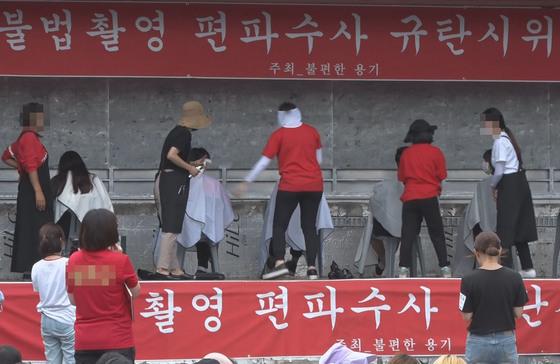 지난달 9일 오후 서울 혜화역 근처에서 다음 카페 '불편한 용기' 주최로 열린 불법 촬영 편파 수사 규탄 집회에서 참가자들이 삭발을 하고 있다. [연합뉴스]