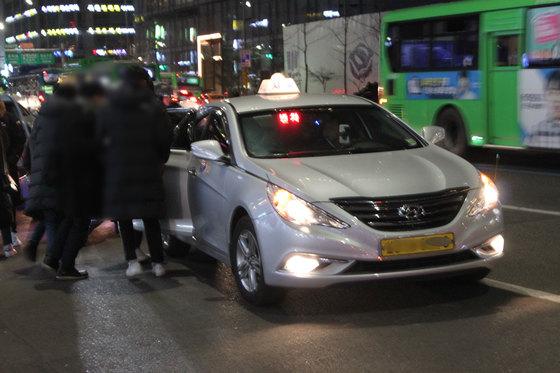 승객들이 승차를 거부하는 택시 기사와 실랑이를 벌이고 있다. [중앙포토]