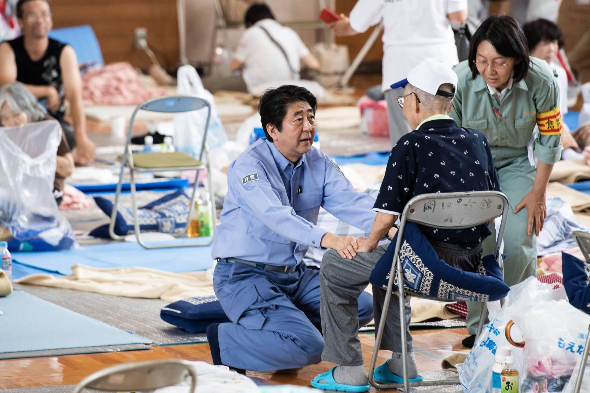 아베 신조(安倍晋三) 일본 총리가 11일(현지시간) 폭우 피해를 본 오카야마 현 구라시키 시에 있는 피난시설을 방문해 무릎을 꿇고 이재민들의 이야기를 듣고 있다. SNS상에서는 지난 5일 밤 기상청의 재난 예보에도 불구 하고 술판을 벌여 여론의 지탄을 받았던 아베 총리가 선거를 앞두고 표심을 고려한 뒤늦은 현장 대처라는 비난이 이어졌다. [AFP=연합뉴스]