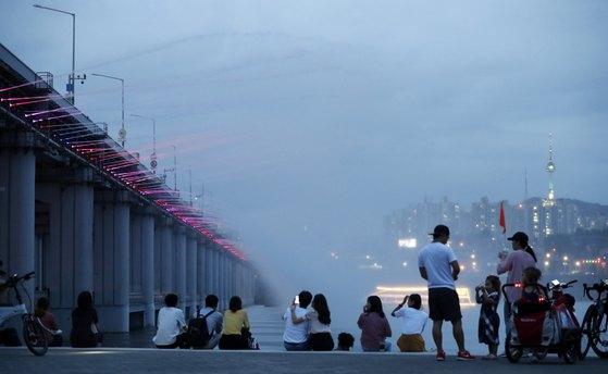 11일 오후 서울 서초구 반포한강공원에서 시민들이 반포대교 달빛무지개분수를 보며 더위를 식히고 있다. 장마 전선이 북한으로 북상하면서 전국 곳곳에 폭염과 열대야 현상이 이어질 전망이다. [뉴스1]
