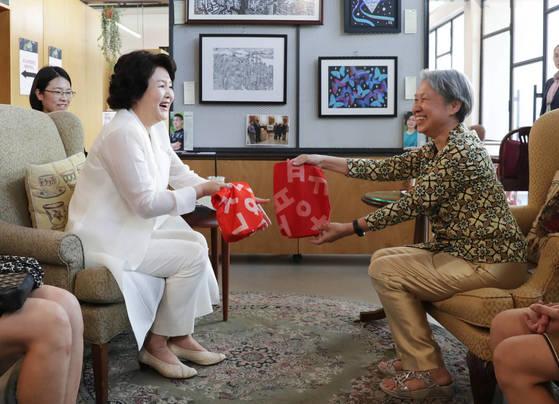 김정숙 여사가 자신이 직접 바느질해 개조한 에코백을 리셴룽 총리의 부인 호칭 여사에게 선물하고 있다. 에코백은 평창올림픽 때 사용된 폐 현수막으로 만든 제품이다. 청와대 사진기자단