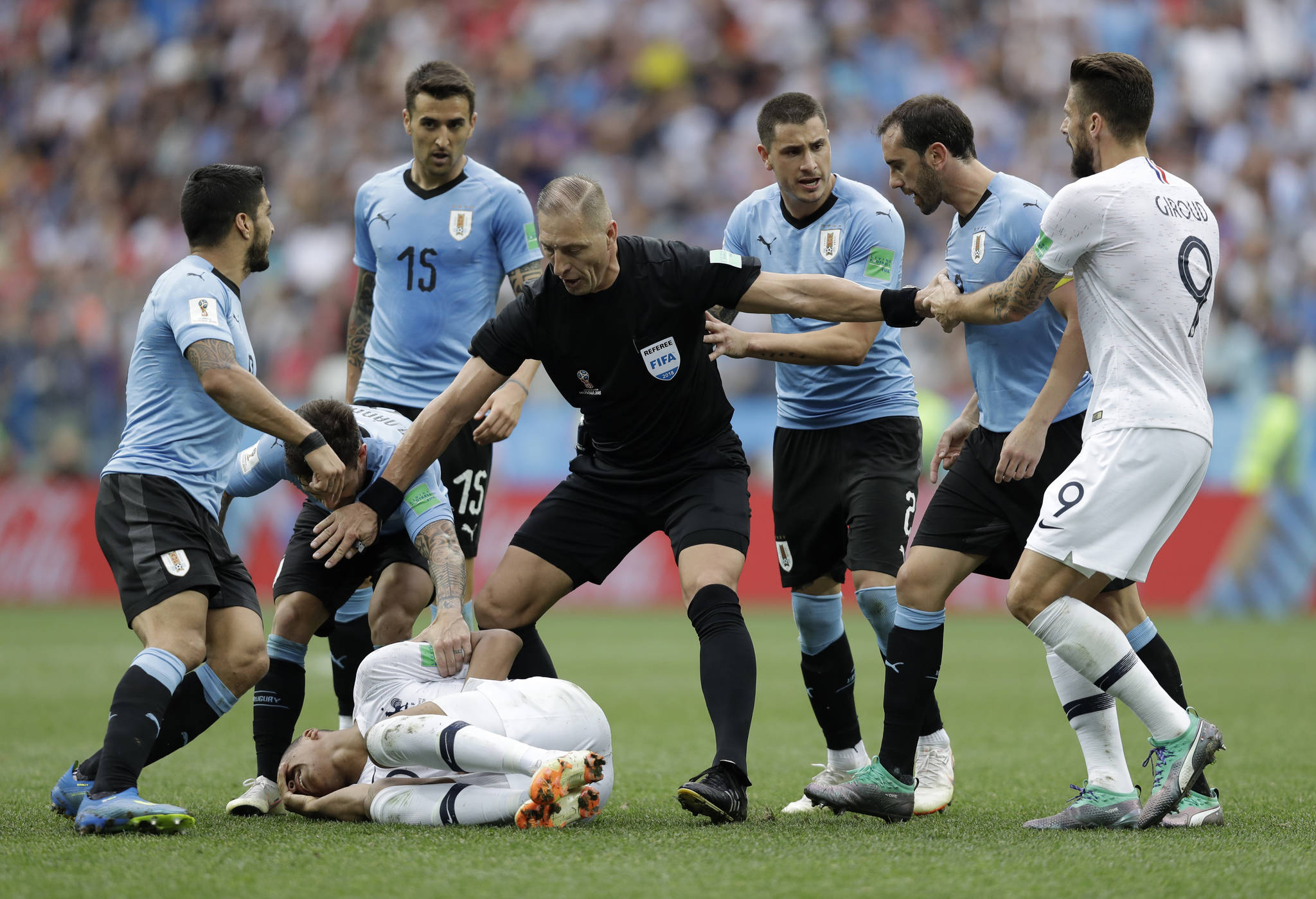 Uruguay players protest to referee Nestor Pitana of Argentina that France's Kylian Mbappe, on the ground, is overreacting after taking a dive during the quarterfinal match between Uruguay and France at the 2018 soccer World Cup in the Nizhny Novgorod Stadium, in Nizhny Novgorod, Russia, Friday, July 6, 2018. (AP Photo/Natacha Pisarenko) <저작권자(c) 연합뉴스, 무단 전재-재배포 금지>