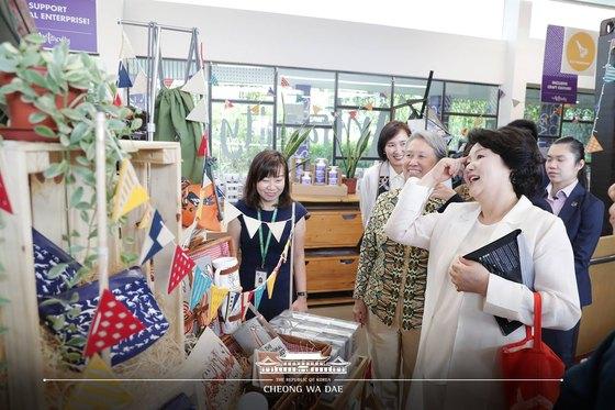 김정숙 여사가 12일(현지시간) 오전 싱가포르 장애인 사회통합 지원센터 이네이블링 빌리지에서 리센룽 총리 부인 호칭 여사와 함께 장애인들이 만든 예술작품들을 둘러보며 구입할 물건을 고르고 있다. 청와대