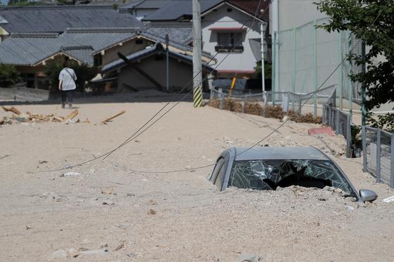 서일본 지역 폭우로 인해 가장 많은 사상자를 낸 히로시마현에서 자동차가 진흙 속에 파묻혀 있다. [EPA=연합뉴스]