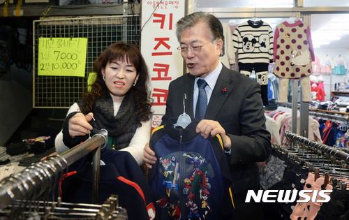 문재인 대통령이 대선 후보 시절이던 지난해 1월 서울의 한 재래 시장에서 손주에게 선물할 옷을 고르고 있다. 김 여사는 '손주가 공룡을 좋아한다'고 했지만, 당시 문 대통령은 로봇 캐리터가 프린트된 옷을 구입했다. 뉴시스