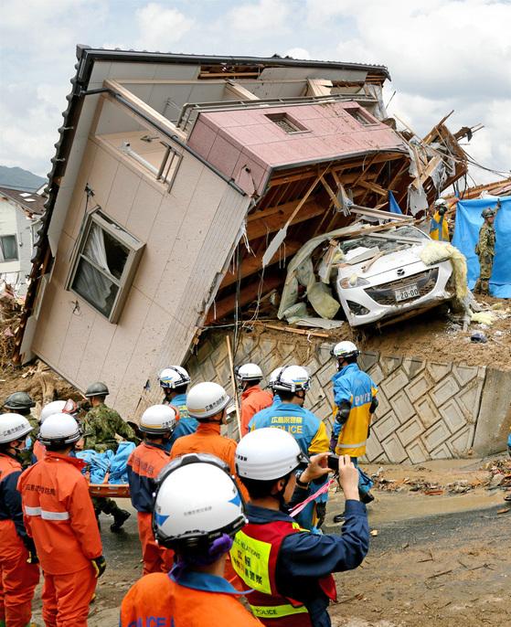 서일본을 덮친 기록적인 폭우로 산사태가 발생한 히로시마(廣島)현 쿠마노 지역에서 9일 경찰 구조대와 자위대가 붕괴된 주택 잔해에서 발견된 희생자를 이송하고 있다. [EPA=연합뉴스]