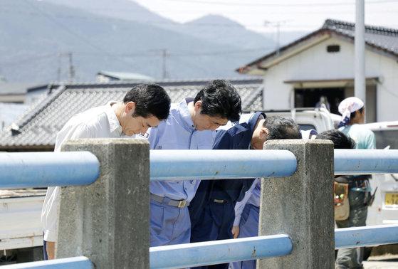 아베 신조 일본 총리가 13일 에히메현을 찾아 수해로 목숨을 잃은 주민들에게 묵념을 하고 있다. [로이터=연합뉴스]