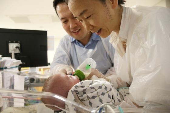 12일 이충구·이인선씨 부부가 딸 사랑이에게 젖병에 담은 모유를 먹이고 있다. 302g으로 태어난 사랑이는 이날 건강하게 퇴원했다. [사진 서울아산병원]