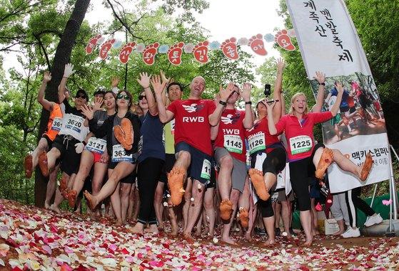 지난 5월 13일 대전 대덕구 장동 계족산에서 열린 '2018 계족산 맨발축제'에 참가한 시민들과 외국인들이 맨발로 황톳길을 걸으며 즐거워하고 있다. [뉴스1]