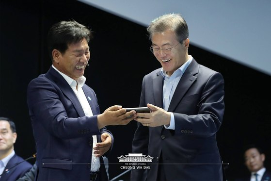문재인 대통령이 지난 5월 17일 서울 강서구 마곡 R&D 단지에서 열린 혁신성장 보고대회에서 스마트폰을 이용한 스마트팜 제어를 체험하고 있다. [뉴스1]
