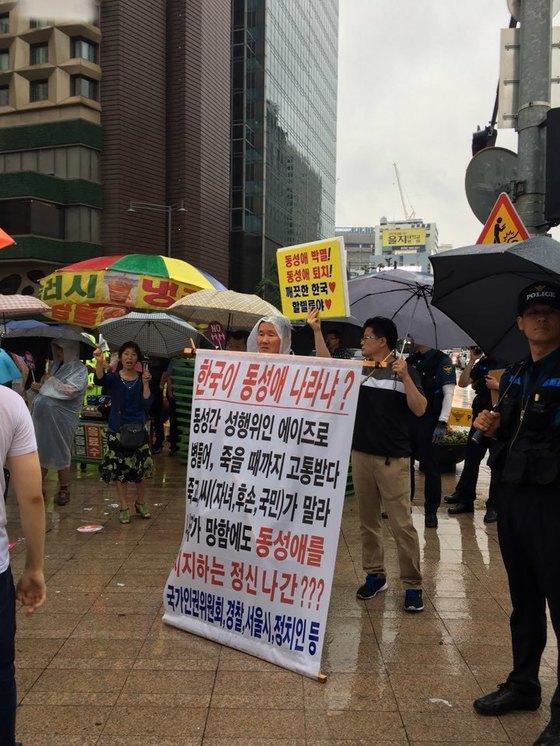 지난해 7월 15일 오후 퀴어축제 행사로 경찰 펜스가 세워진 서울광장 바깥에서는 동성애에 반대하는 사람들이 시위를 벌이고 있다. 홍상지 기자