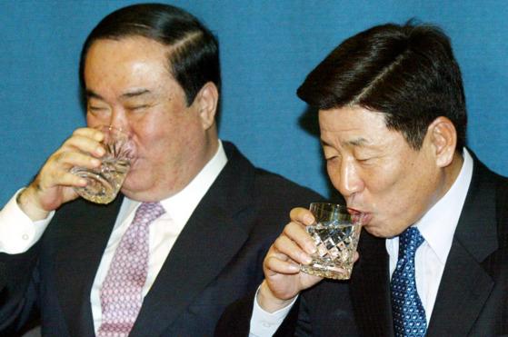 문희상 전 대통령 비서실장(왼쪽)과 유인태 전 정무수석이 2004년 청와대 춘추관에서 총선 출마 기자간담회를 하던 도중 물을 마시고 있다. [중앙포토]