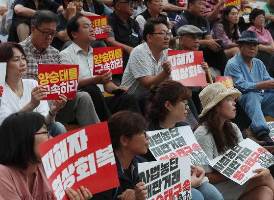 12일 오후 서울 종로구 세종문화회관 계단에서 열린 양승태 사법농단 2차 고발대회에서 참가자들이 손팻말을 들고 있다. [연합뉴스]
