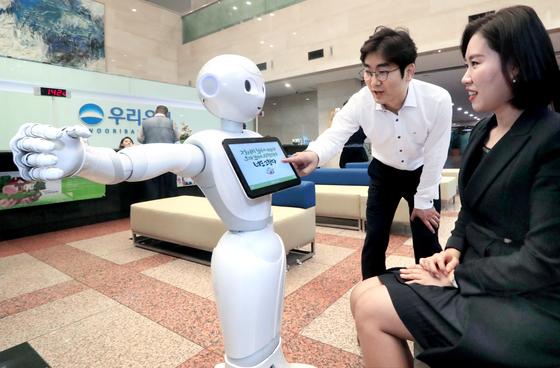로봇 은행원 '페퍼(Pepper)'가 지난해 10월 서울 회현동 우리은행 본점에 첫 출근 했다. 소프트뱅크로보틱스의 인공지능 로봇 페퍼는 영업장 안내 등 고객서비스를 제공한다. [중앙포토]