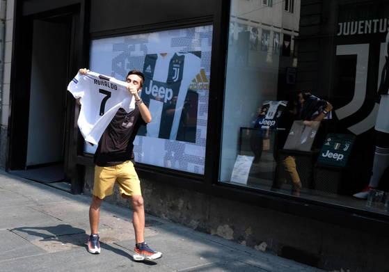 유벤투스 팬이 지난 11일 구단 공식 스토어에서 호날두의 새 유니폼을 구매한 뒤 자랑스럽게 펼쳐보이고 있다. [EPA=연합뉴스]