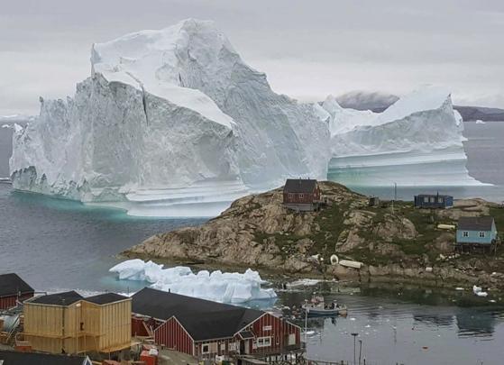 그린랜드 서쪽 해안 마을로 떠내려온 거대한 빙산. 지난 12일 촬영된 사진이다. 빙산이 녹아 쪼개질 경우 쓰나미가 발생해 마을을 덮칠 수 있다. [AP=연합뉴스]