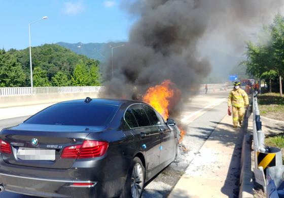 15일 경북 영주시 장수면 중앙고속도로 춘천 방향 영주휴게소 입구에서 BMW 520d 승용차 엔진룸에서 불이 나 소방대원들이 진화에 나서고 있다. [영주소방서 제공]