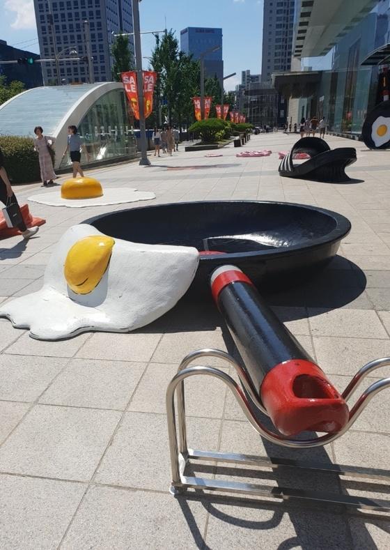 대구·경북 모든 지역에 폭염특보가 내려진 15일 오후 현대백화점 대구점 앞에서 시민들이 더위에 익은 달걀프라이와 녹아내린 슬리퍼 조형물 사이를 지나가고 있다. [연합뉴스]