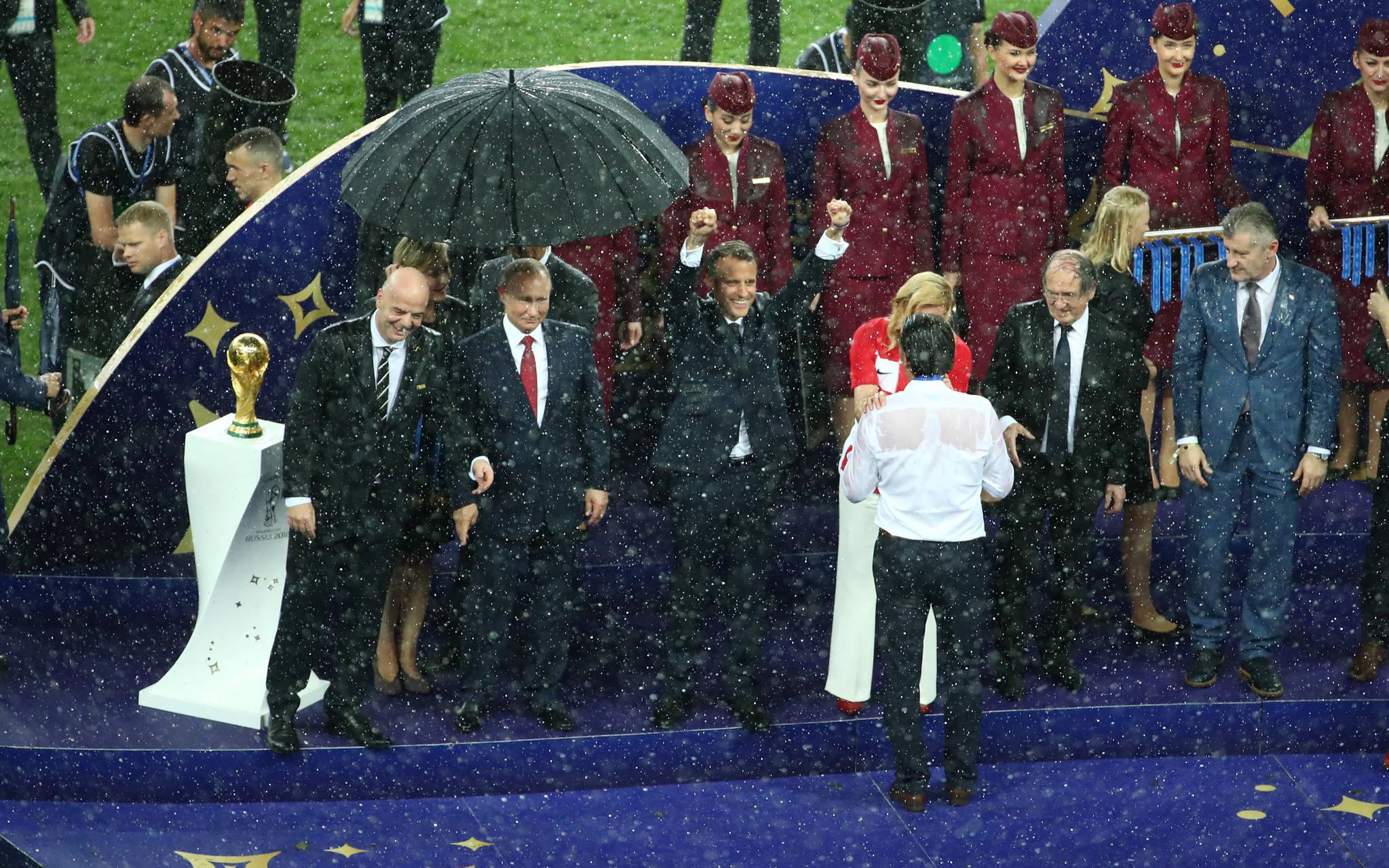 15일(현지시간) 프랑스와 크로아티아의 결승전 직후 열린 시상식에서 선수들을 격려하는 콜린다 그라바르 키다로비치 크로아티아 대통령과 엠마누엘 마크롱 프랑스 대통령. [로이터=연합뉴스]