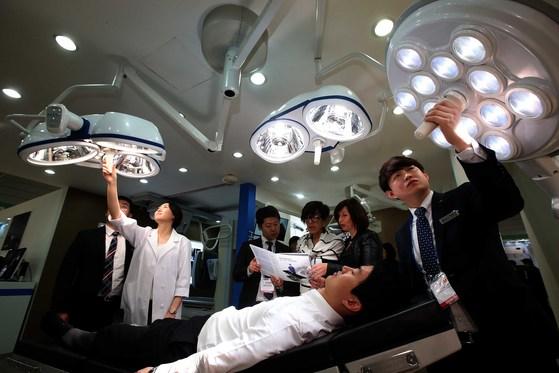 국내 최대 의료기기 전시회인 'KIMES 2016(국제 의료기기·병원설비 전시회)'에 참가한 한 업체가 수술대에 그림자가 생기지 않는 조명기구를 선보였다(본문과 연관없는 사진). [중앙포토]