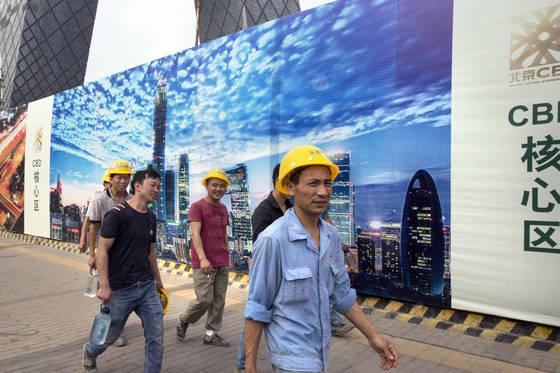 지난 10일 중국 베이징 상업중심지 건설 현장에서 인부들이 걸어가고 있다. [베이징 AP=연합뉴스]
