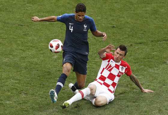 France's Raphael Varane, left, and Croatia's Mario Mandzukic challenge for the ball during the final match between France and Croatia at the 2018 soccer World Cup in the Luzhniki Stadium in Moscow, Russia, Sunday, July 15, 2018. (AP Photo/Frank Augstein) <저작권자(c) 연합뉴스, 무단 전재-재배포 금지>