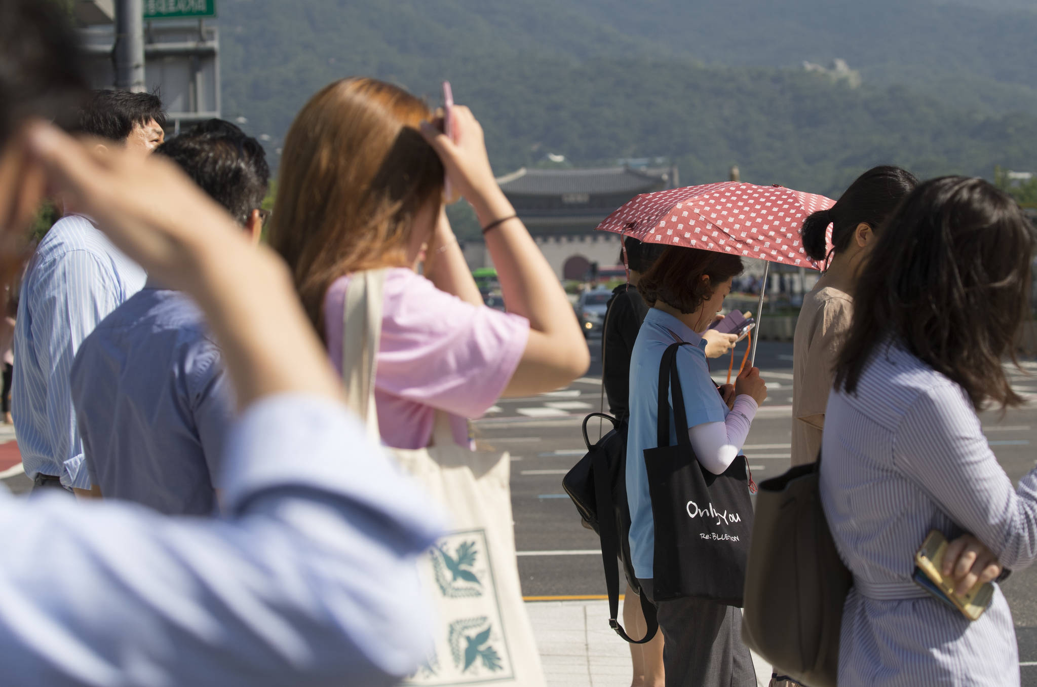 폭염이 이어지는 17일 서울 세종로사거리에서 시민들이 햇빛을 가린 채 보행 신호를 기다리고 있다. [연합뉴스]