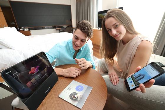 18일 서울 동대문 인근에 있는 노보텔 앰배서더 동대문 호텔 객실에서 모델들이 기가지니 인공지능 서비스를 선보이고 있다. [사진 KT]