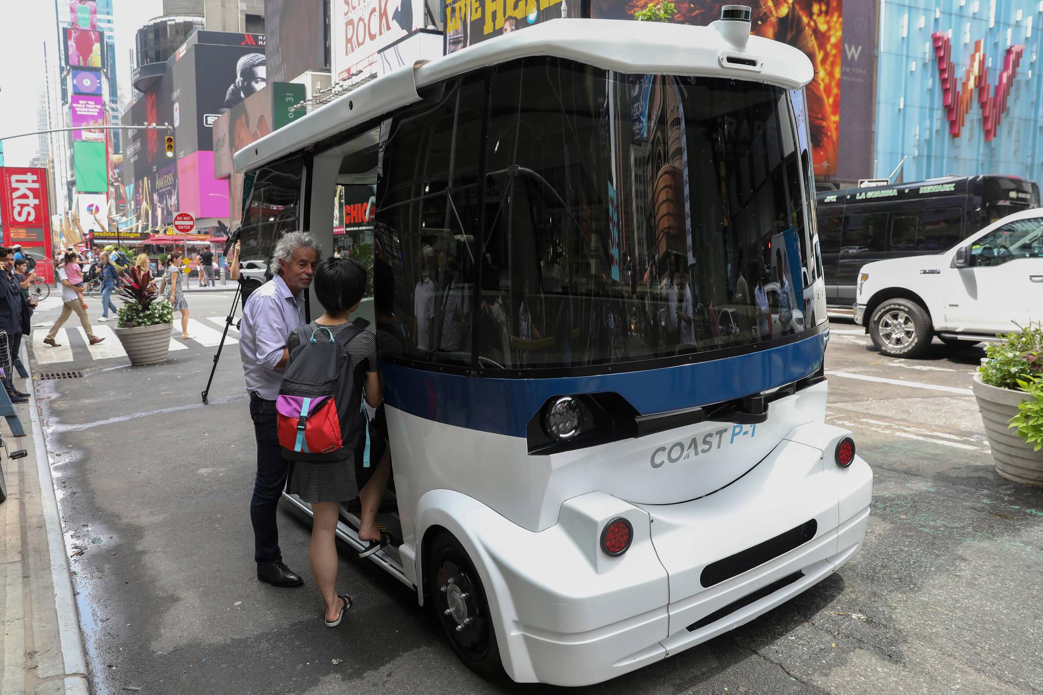 저속으로 운행하는 전기자율주행버스 '코스트 P1'이 17일 뉴욕 맨해튼에서 첫 시험운행했다.공개행사에 참석한 취재진이 차량에 탑승하고 있다.[로이터=연합뉴스]