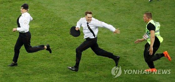 15일(현지시간) 러시아 모스크바 루즈니키 스타디움에서 열린 2018 러시아 월드컵 크로아티아-프랑스 결승전에서 경기 관계자(오른쪽)가 경기장에 난입한 관중의 뒤를 쫓고 있다. [연합뉴스]