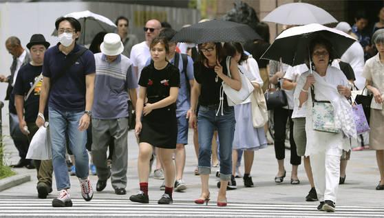 지난 14일 일본 전국에 폭염이 쏟아지며 일사병과 열사병 등 온열질환으로 인한 사망자가 6명 발생한 가운데 도쿄(東京) 긴자(銀座)에서 행인들이 양산을 쓴 채 걸어가고 있다. [연합뉴스]