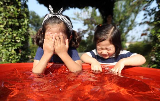 폭염이 계속되는 19일 오후 경남 함안군 한 가정집에서 어린이들이 대야 담긴 물로 더위를 식히고 있다. [연합뉴스]