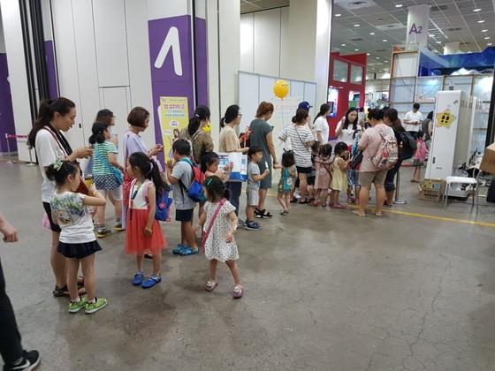캐릭터 라이선싱 페어의 A홀~B홀 사이 스포키즈 포토존 앞에서 아이들이 줄지어 기다리고 있다.