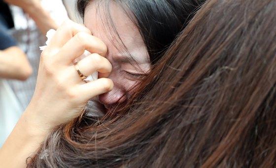 철도노사가 KTX 해고 승무원 복직을 합의한 21일 12년째 투쟁을 이어온 KTX 해고 승무원들이 서울역 플랫폼 중앙계단에서 투쟁 해단식 기자회견을 하며 부둥켜안고 눈물을 흘리고 있다. [연합뉴스]