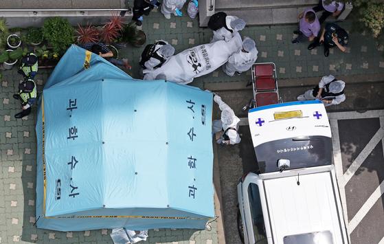 23일 노회찬 정의당 원내대표가 사망한 서울 중구 한 아파트에서 경찰 과학수사대원들이 시신을 구급차로 옮기고 있다. [뉴스1]