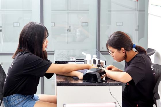 김다현 학생이 동갑내기 친구 김한설 학생모델에게 직접 네일아트를 해주고 있다.