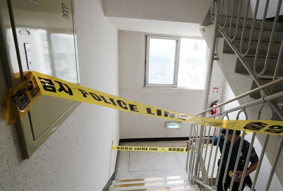 정의당 노회찬 원내대표가 23일 투신 자살한 서울 중구 남산타운 아파트 17층과 18층 사이 계단에서 경찰이 폴리스 라인을 설치하고 있다. 임현동 기자