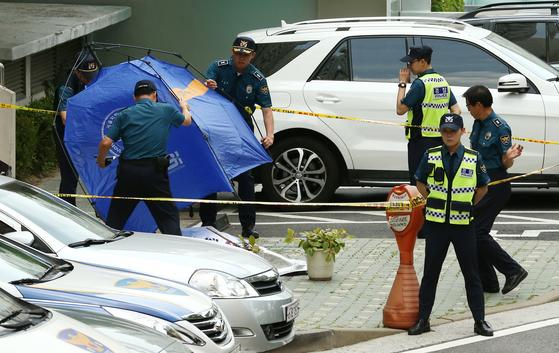 23일 정의당 노회찬 원내대표가 투신한 서울 중구 남산타운 아파트에서 경찰이 시신을 덮은 텐트가 바람에 넘어가자 급히 옮기고 있다. 임현동 기자
