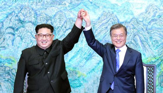 문재인 대통령(오른쪽)과 김정은 국무위원장이 지난 5월 27일 오후 판문점 평화의 집에서 열린 남북정상회담에서 한반도의 평화와 번영, 통일을 위한 판문점 선언문에 서명 후 서로 손을 잡고 위로 들어보이고 있다. [청와대사진기자단]