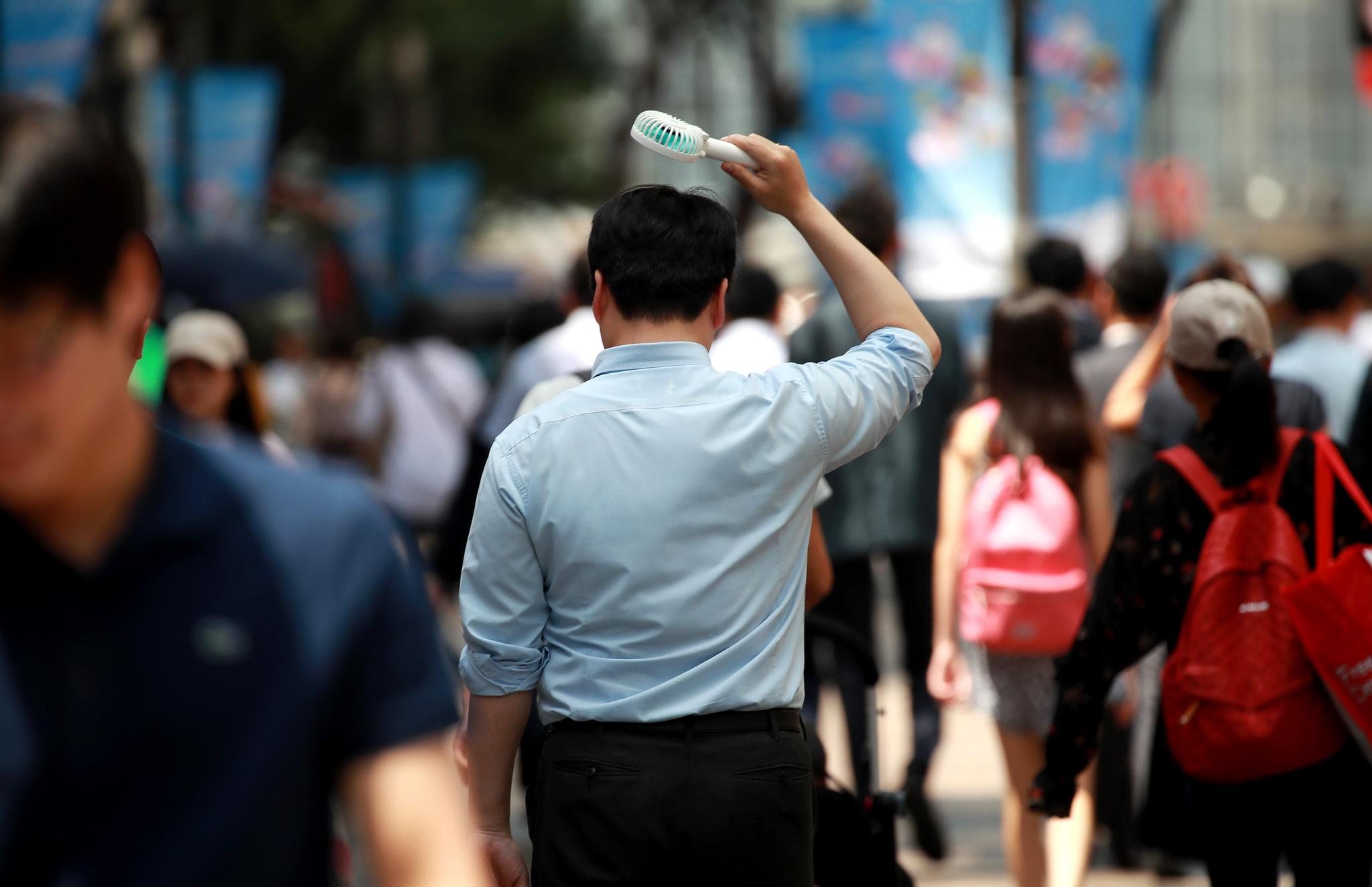 24일 서울 명동 거리에서 한 직장인이 휴대용 선풍기와 함께 거리를 걷고 있다. [연합뉴스]