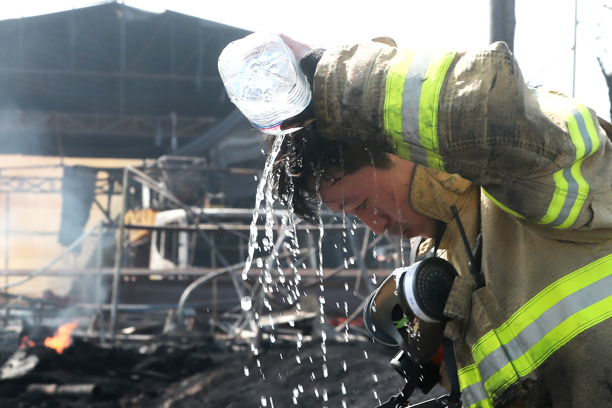 119안전센터 소방대원이 화재 현장 정리를 마치고 물로 더위를 식히고 있다. [뉴스1]