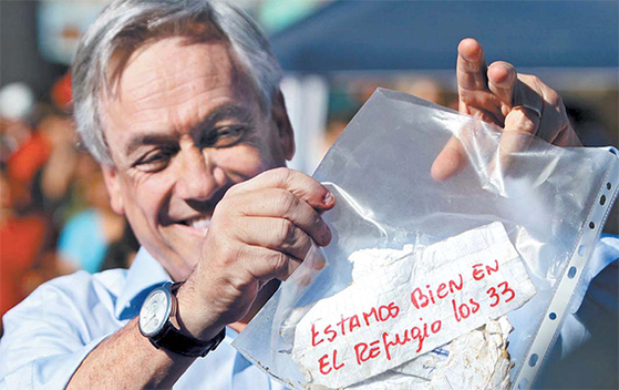 세바스찬 피녜라 전 칠레 대통령이 매몰 광부들이 보낸 쪽지를 들어 보이며 환호하고 있다. [AFP=연합뉴스]