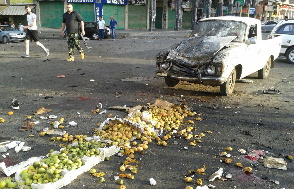 시리아 공영 사나통신이 배포한 사진. 25일 스웨이다 남쪽에서 벌어진 트럭 자살 테러 현장을 군인이 지나쳐가는 모습. IS세력은 일련의 자살테러로 적어도 40명을 숨지게 했다. [SANA=AFP=연합뉴스]