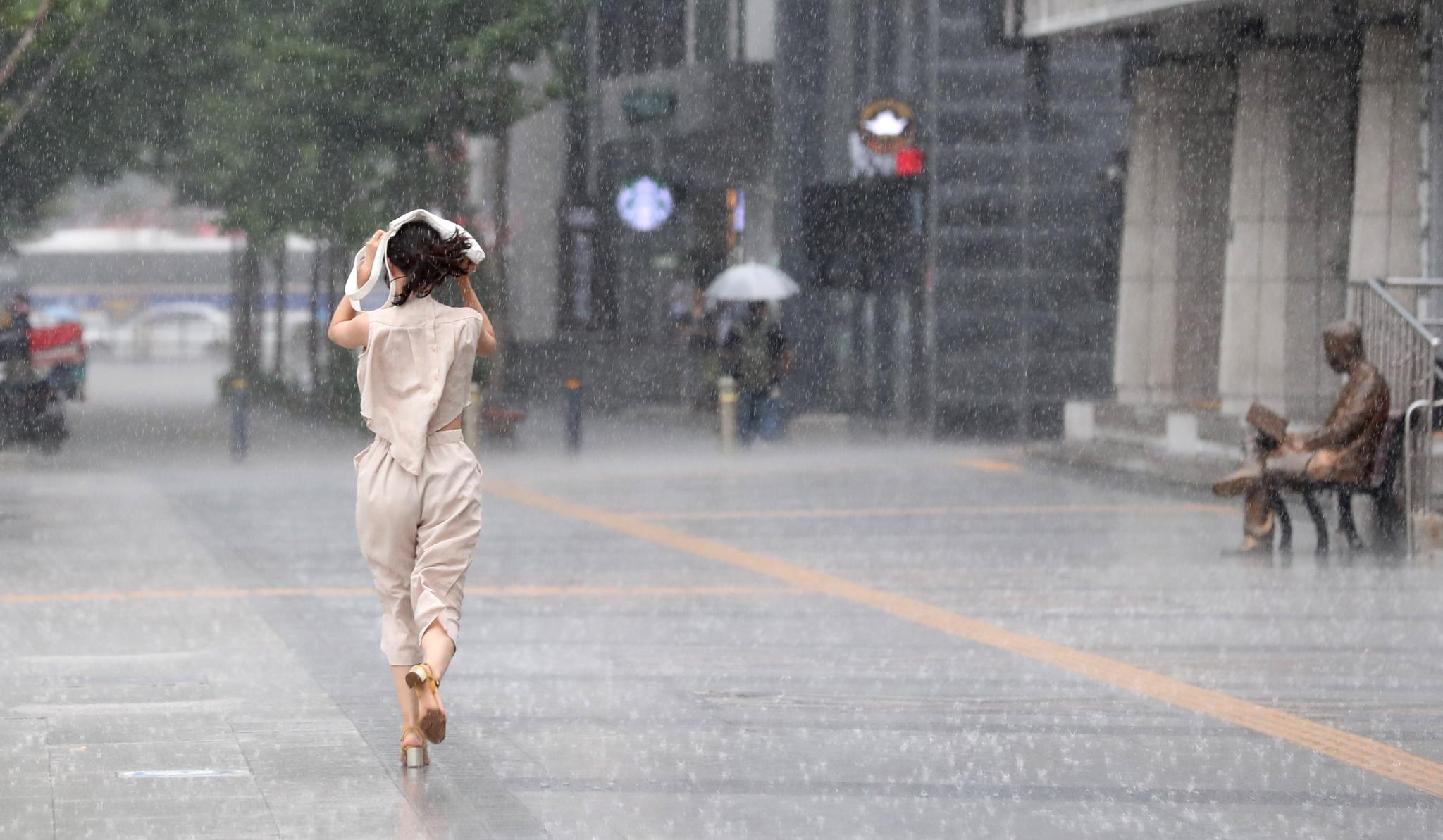 폭염이 계속된 28일 서울 광화문 광장 주변에 한때 강한 소나기가 내리자 시민들이 비를 피하기 위해 뛰고 있다. [연합뉴스]