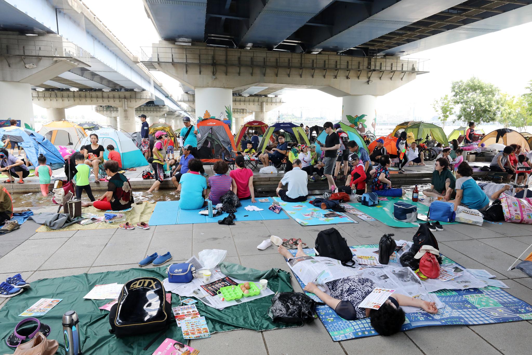 전국적으로 폭염이 이어지는 29일 서울 영등포구 여의도 한강공원을 찾은 시민들이 마포대교 아래에서 더위를 식히고 있다. [뉴스1]