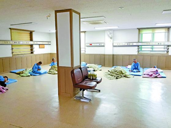 """경남 한 요양병원 병실에 환자들이 바닥에 침구를 깔고 누워 있다. 병원 측은 '치매 환자가 낙상할 위험이 있어 온돌방 형태의 병실을 운영 중""""이라고 했다. 전문가에 따르면 이런 형태의 병실이 위법은 아니나 호출벨이 환자 위쪽 벽면에 설치돼 있어 위급 상황 시 이용이 어려울 수 있다고 지적했다. [위성욱 기자]"""