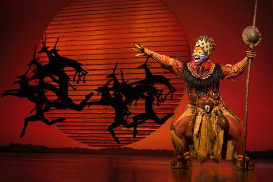 뮤지컬 '라이온 킹'의 첫 장면. 대표 넘버 '서클 오브 라이프'를 부르는 개코원숭이 주술사 라피키 뒤로 붉은 태양이 떠오르고, 퍼펫과 혼연일체가 돼 가젤 연기를 하는 배우들이 보인다. [사진 디즈니]
